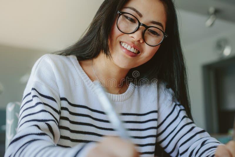 Ragazza sorridente con gli occhiali che studia a casa fotografia stock libera da diritti