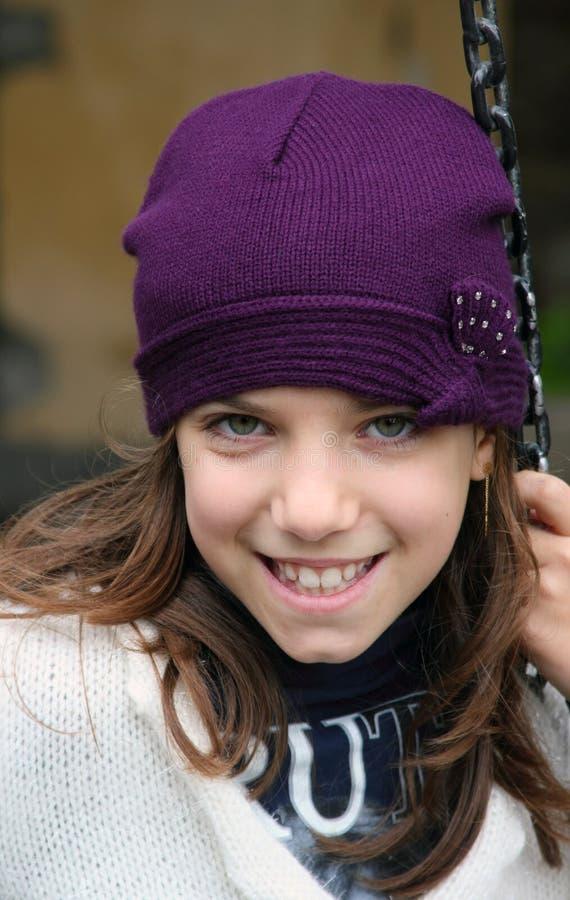 Ragazza sorridente con il cappello viola fotografie stock
