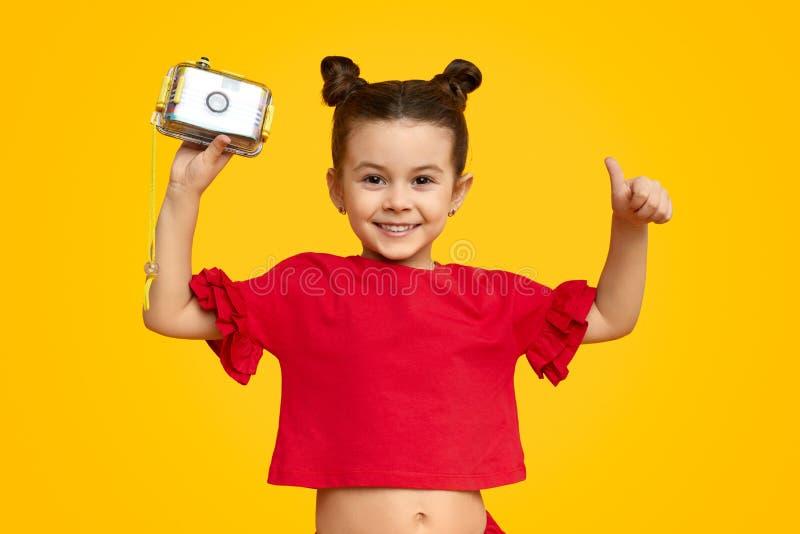 Ragazza sorridente con la macchina fotografica della foto che gesturing pollice su fotografia stock libera da diritti