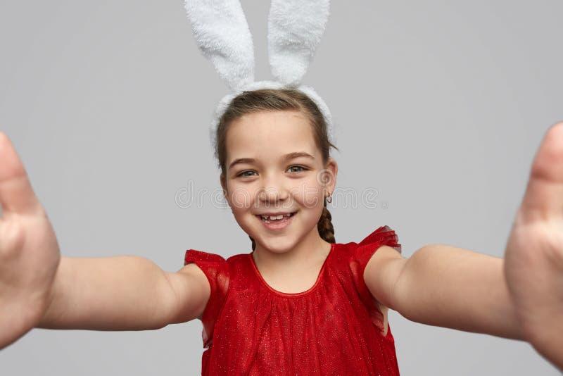 Ragazza sorridente con le orecchie del coniglietto che prendono selfie immagini stock libere da diritti