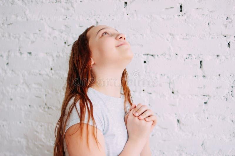 Ragazza sorridente dell'adolescente della bella testarossa affascinante che fa un desiderio isolato sul muro di mattoni bianco fotografia stock libera da diritti