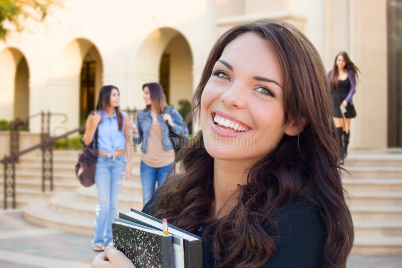 Ragazza sorridente della corsa mista con i libri che cammina sulla città universitaria fotografie stock libere da diritti