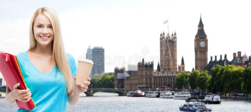 Ragazza sorridente dello studente con le cartelle e la tazza di caffè fotografie stock libere da diritti