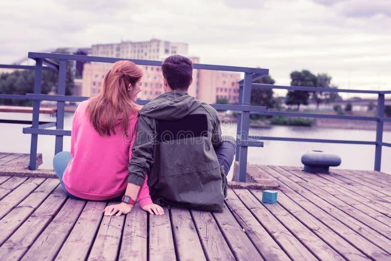 Ragazza sorridente dello zenzero in maglia con cappuccio rosa che si siede vicino al suo ragazzo dai capelli corti immagini stock