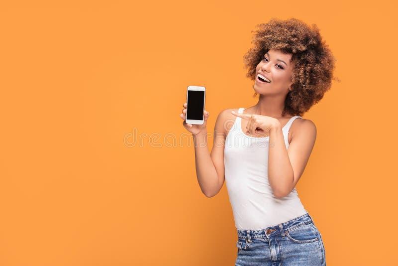 Ragazza sorridente di afro che mostra il telefono cellulare dello schermo in bianco fotografie stock