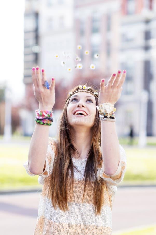 Ragazza sorridente di hippy che gioca con le margherite, all'aperto. immagini stock