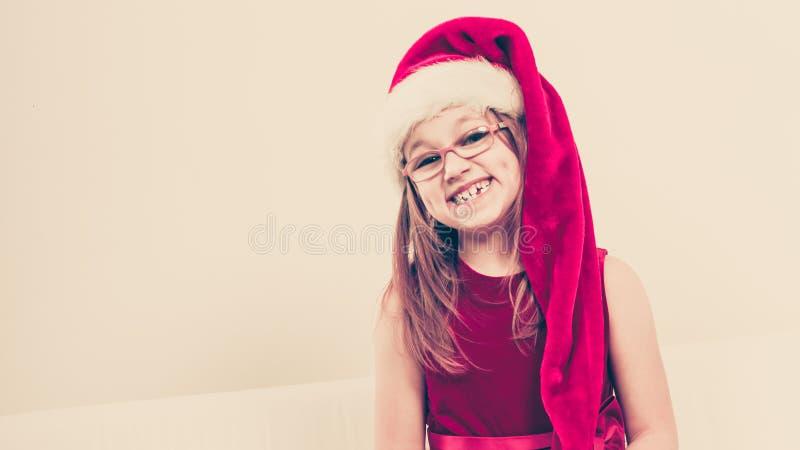 Ragazza sorridente di natale in attrezzatura festiva del cappello di Santa fotografie stock libere da diritti