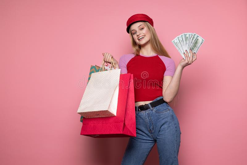 Ragazza sorridente felice in cappello rosso d'avanguardia che tiene i sacchetti della spesa variopinti immagine stock libera da diritti