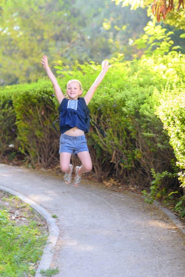 Ragazza sorridente felice che salta sul parco nel tempo di giorno immagini stock