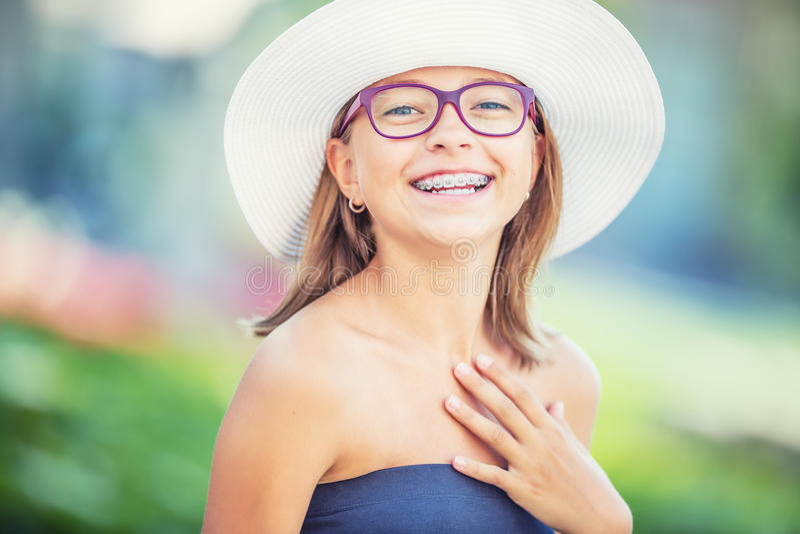Ragazza sorridente felice con i ganci ed i vetri dentari Ganci e vetri d'uso dei denti della giovane ragazza bionda caucasica sve fotografia stock