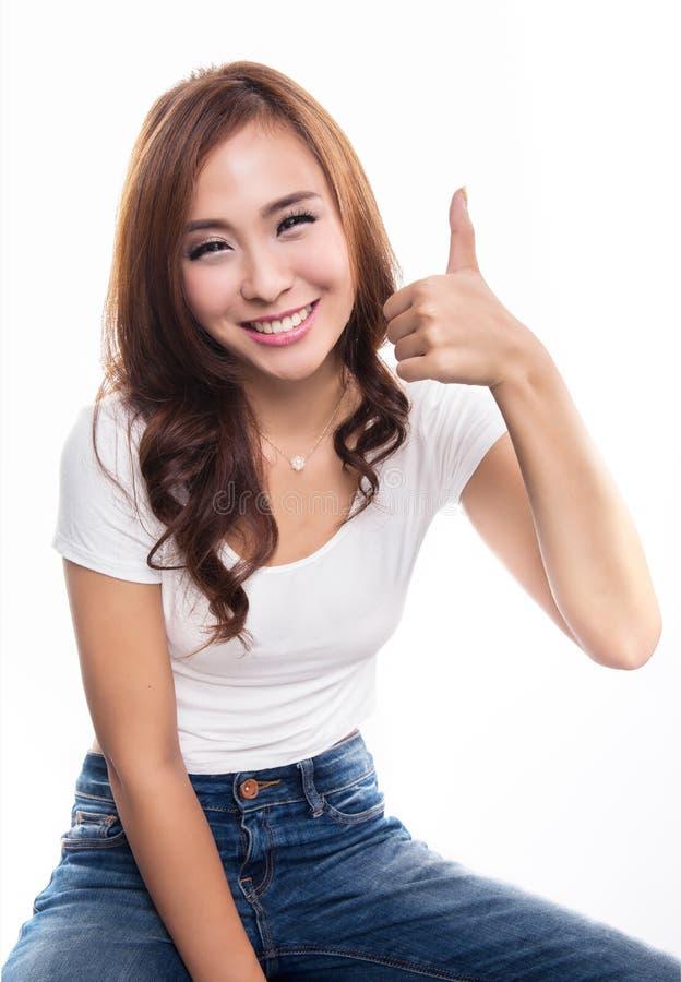Ragazza sorridente felice con i pollici sul gesto, isolato sul BAC bianco fotografia stock libera da diritti