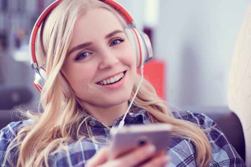 Ragazza sorridente felice nella musica dell'abbigliamento casual e nelle canzoni d'ascolto di selezione su uno Smart Phone che si fotografia stock