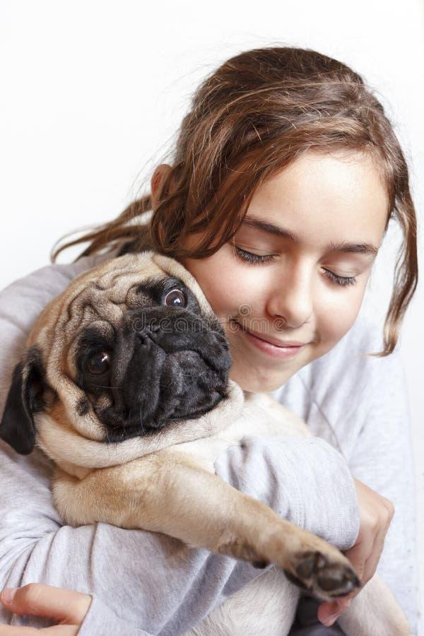 Ragazza sorridente graziosa felice dell'adolescente che abbraccia il cane del carlino con amore fotografie stock libere da diritti