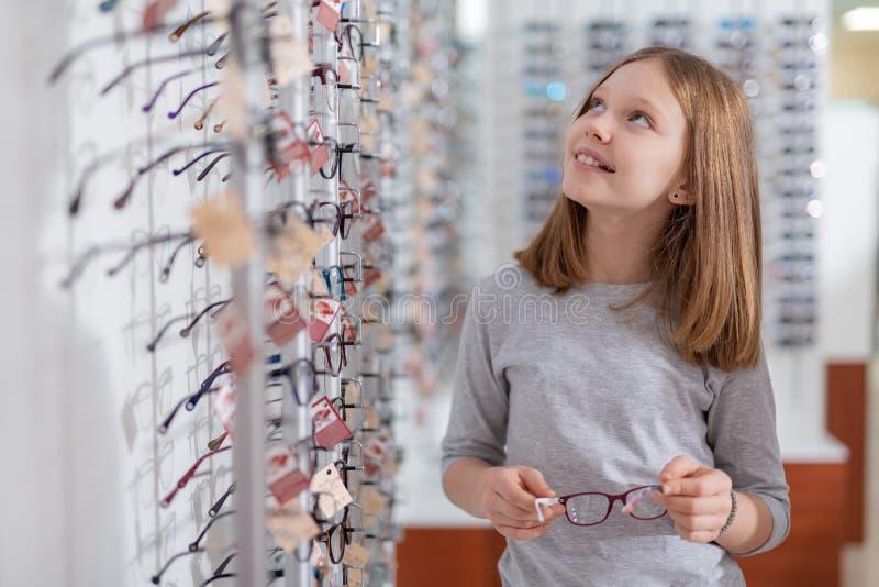Ragazza sorridente piacevole che sceglie i vetri al deposito ottico immagini stock libere da diritti