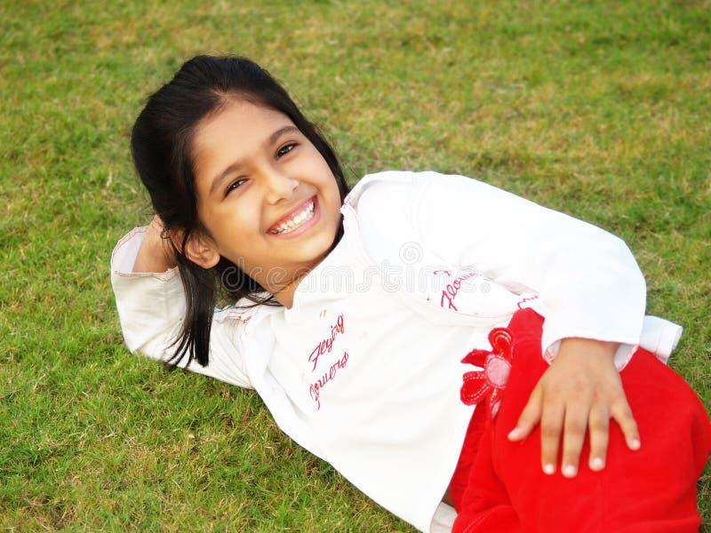 Ragazza sorridente su erba fotografie stock libere da diritti