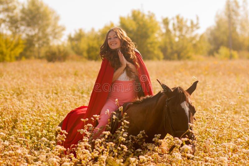 ragazza sorridente su un cavallo in un mantello immagine stock
