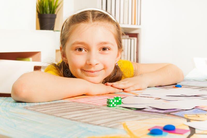 Ragazza sorridente sveglia che si siede alla tavola di gioco fotografia stock libera da diritti