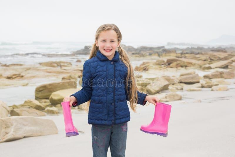 Ragazza sorridente sveglia che tiene i suoi stivali di gomma alla spiaggia fotografia stock