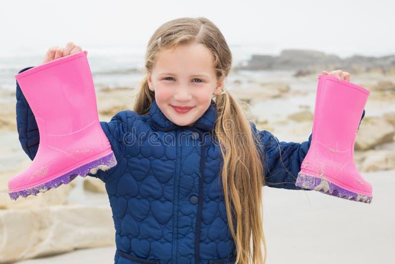 Ragazza sorridente sveglia che tiene i suoi stivali di gomma alla spiaggia immagine stock libera da diritti