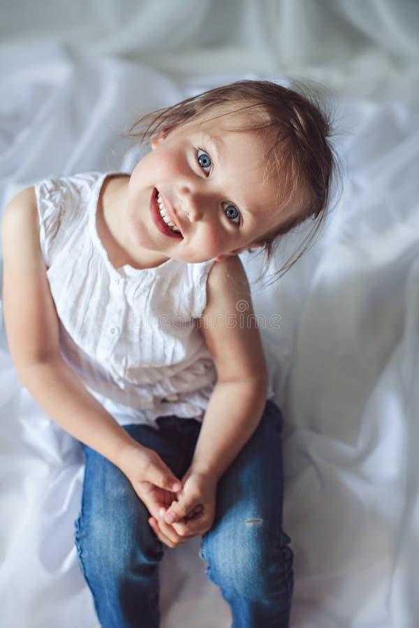 Ragazza sorridente sveglia con gli occhi azzurri immagine stock