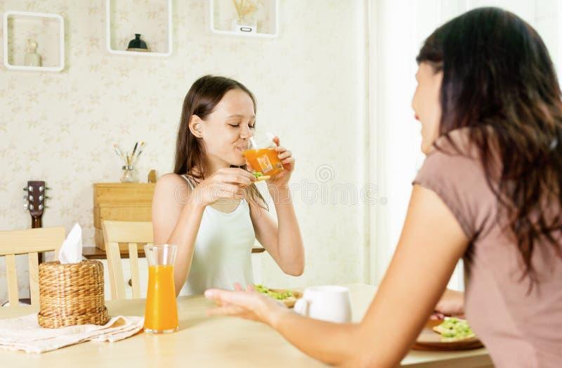 Ragazza sorridente sveglia del preteen che mangia prima colazione sana con la mamma: panino e succo d'arancia dell'avocado Concet immagini stock libere da diritti