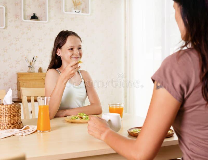 Ragazza sorridente sveglia del preteen che mangia prima colazione sana con la mamma: panino e succo d'arancia dell'avocado Concet immagini stock