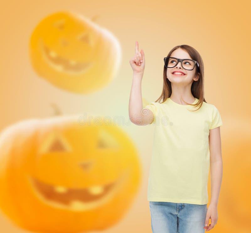 Ragazza sorridente in vetri sopra il fondo delle zucche immagini stock libere da diritti