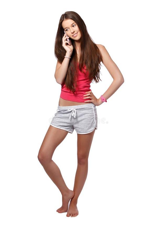 Ragazza sottile piacevole del brunette che fa una chiamata immagine stock libera da diritti