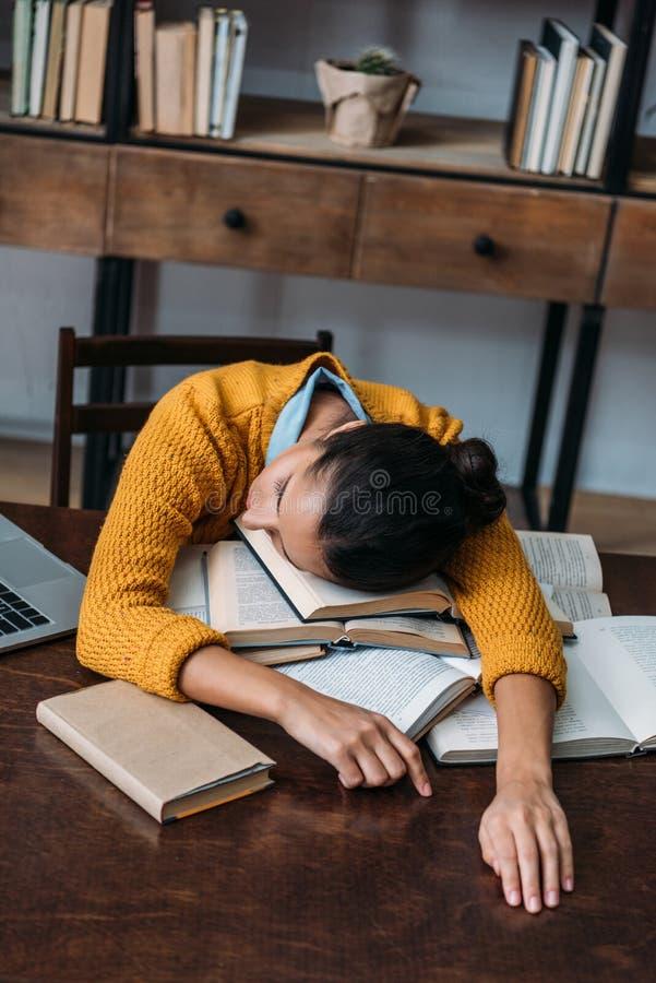 ragazza sovraccarica dello studente che dorme alla biblioteca mentre preparando per l'esame fotografie stock libere da diritti