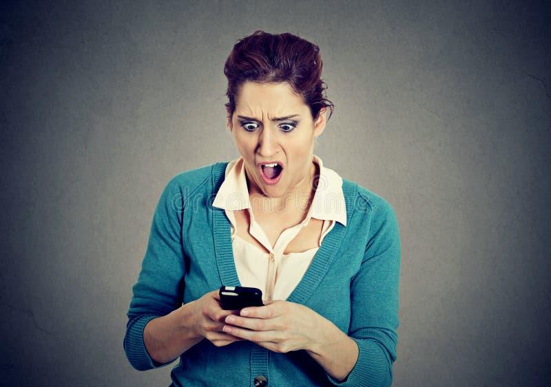Ragazza spaventata ansiosa colpita che esamina telefono che vede le foto di cattive notizie fotografie stock