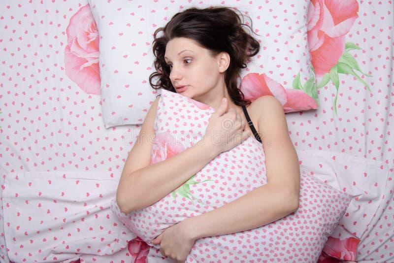 Ragazza spaventata che abbraccia un cuscino mentre trovandosi a letto immagini stock libere da diritti