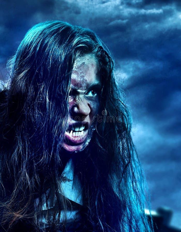 Ragazza spaventosa dello zombie del non morto sul cimitero di Halloween alla notte fotografia stock