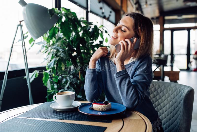 Ragazza splendida che parla sul telefono mentre riposando al caffè fotografie stock