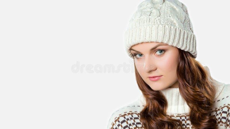 Ragazza splendida che porta il saltatore tricottato caldo di natale e un cappello, concetto di natale su fondo bianco immagine stock libera da diritti