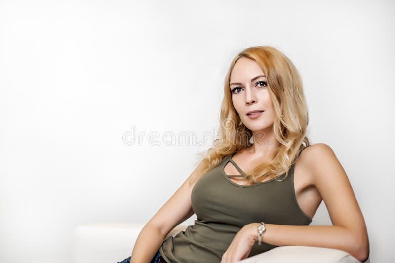 Ragazza splendida con il bello fronte che si siede sul sofà bianco immagini stock libere da diritti