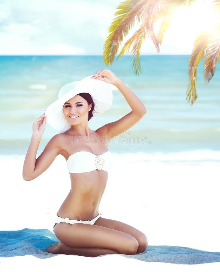 Ragazza splendida e bella che si rilassa su una spiaggia di estate immagine stock