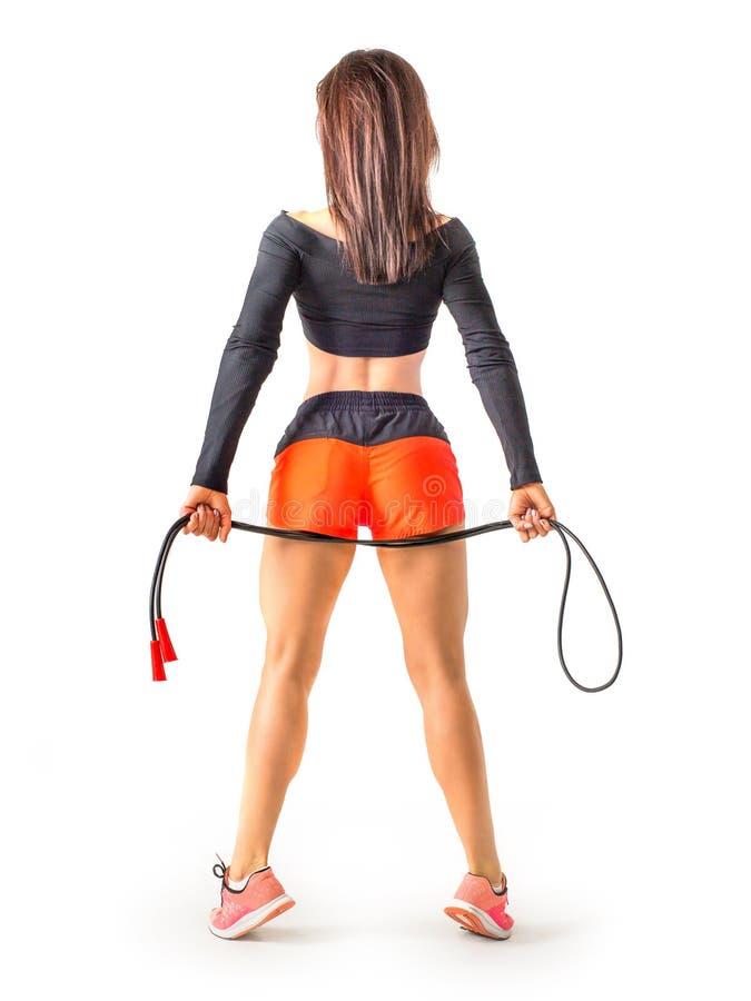 Ragazza sportiva attraente con un salto della corda Foto della ragazza in abiti sportivi isolati su fondo bianco Vista dalla part fotografia stock