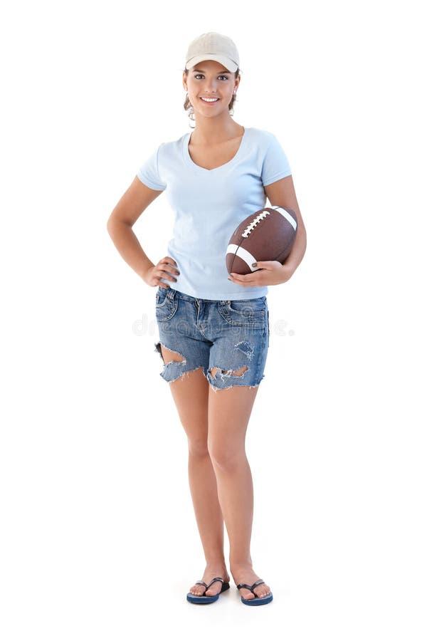 Ragazza sportiva con sorridere di football americano immagini stock libere da diritti