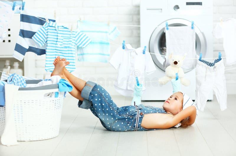 Ragazza stanca del bambino del piccolo assistente per lavare i vestiti e resto nel laund fotografia stock