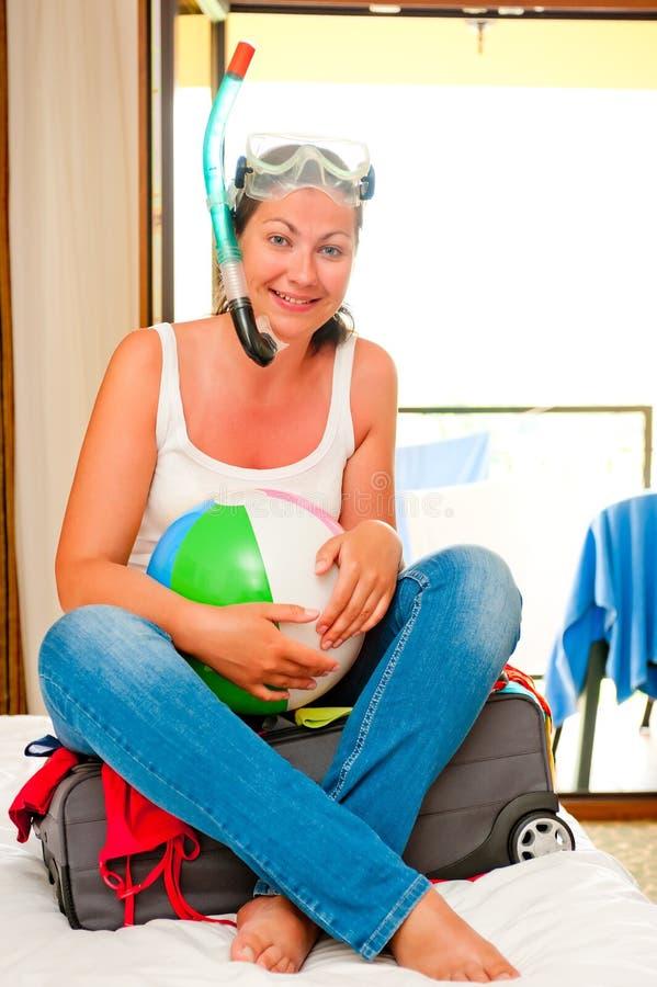 Ragazza su una valigia con una maschera e una palla fotografie stock libere da diritti