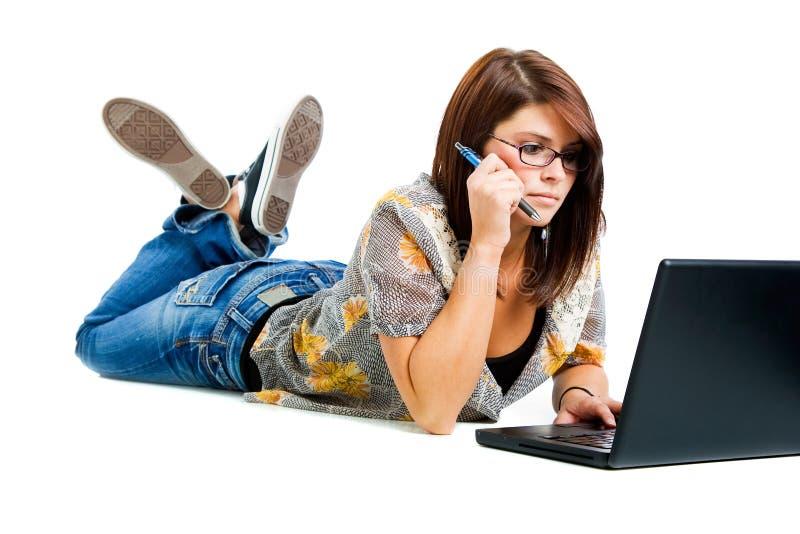Ragazza sul computer portatile che tiene una penna fotografia stock libera da diritti
