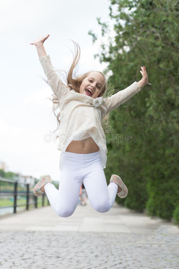 Ragazza sul fronte sorridente felice, natura su fondo Concetto di felicità Ragazza del bambino con il salto allegro di espression immagini stock