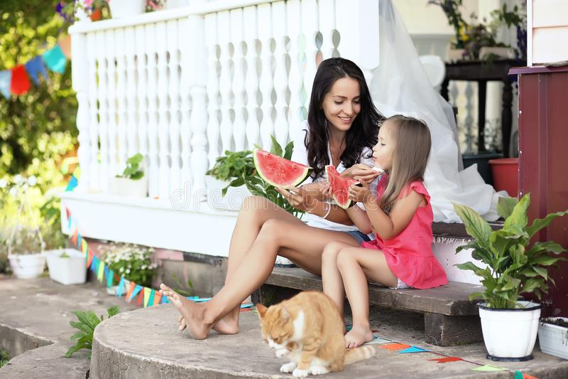 Ragazza sul portico della casa che mangia anguria dolce immagini stock