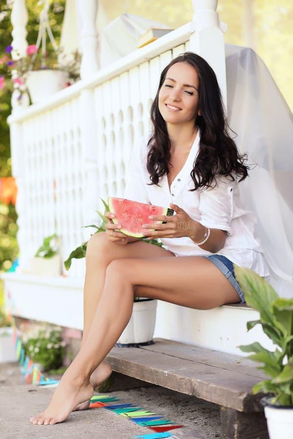 Ragazza sul portico della casa che mangia anguria dolce fotografie stock