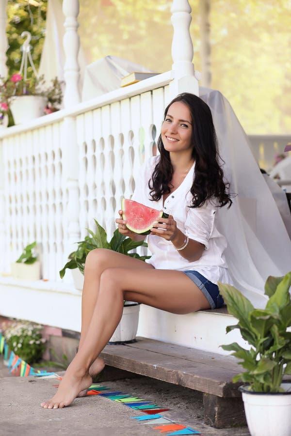 Ragazza sul portico della casa che mangia anguria dolce immagine stock libera da diritti
