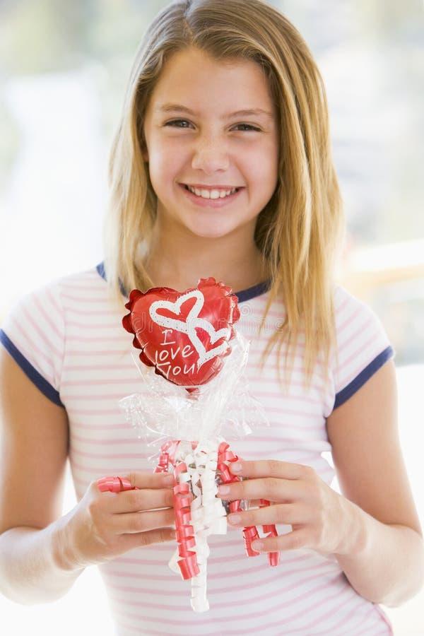 Ragazza sull'aerostato di amore della holding di giorno del biglietto di S. Valentino fotografia stock