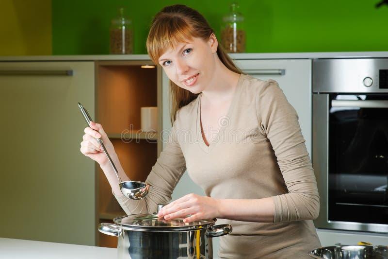 Ragazza sulla cucina con una siviera fotografie stock