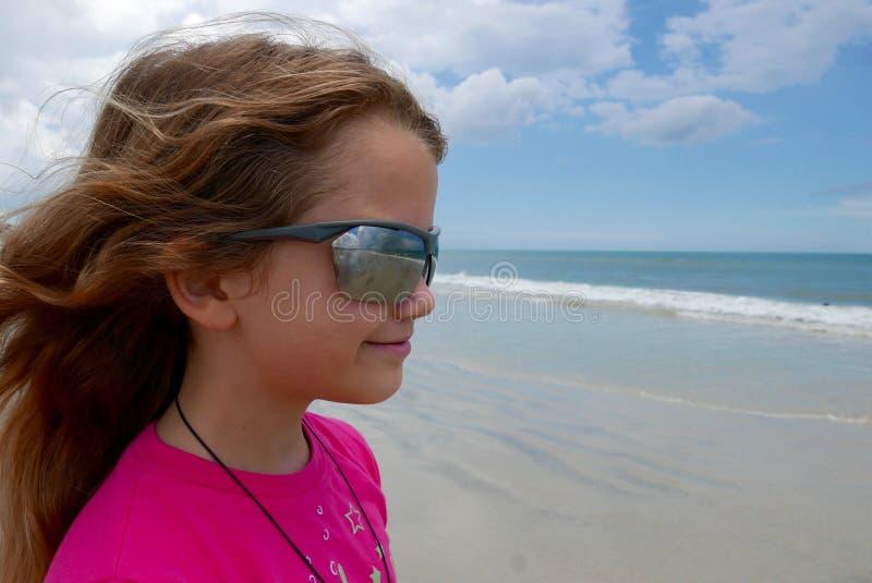 Ragazza sulla spiaggia che guarda fuori all'oceano con le onde che riflettono in suoi occhiali da sole immagine stock