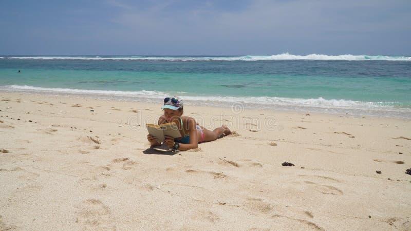 Ragazza sulla spiaggia che legge un libro fotografia stock