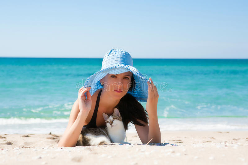 Ragazza sulla spiaggia con un gattino fotografia stock libera da diritti